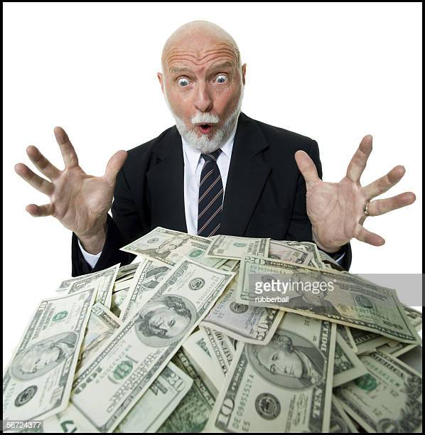Close-up of a businessman looking at a pile of money