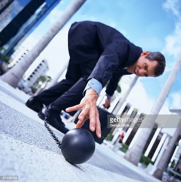 close-up of a businessman reaching for the ball of the shackles on his ankles