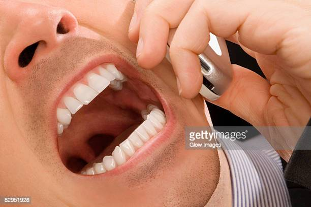 close-up of a businessman shouting on a mobile phone - uvula stock photos and pictures