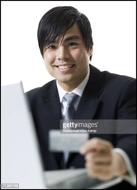 Close-up of a businessman sitting in front of a laptop and holding a credit card