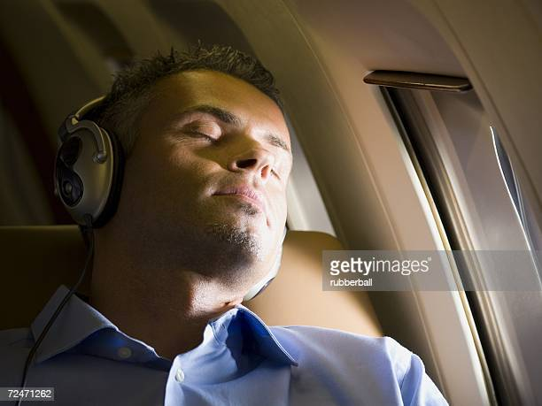 Close-up of a businessman sleeping and  listening to music on headphones in an airplane