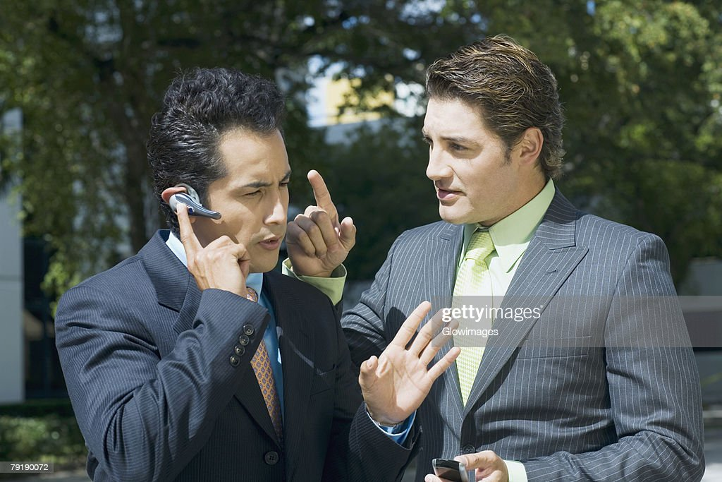Close-up of a businessman talking on a hands free device with another businessman standing beside him : Stock Photo