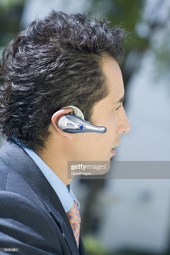 Close-up of a businessman wearing a hands free device : Stock Photo