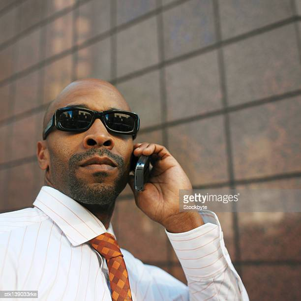 close-up of a businessman wearing sun glasses talking on a mobile phone - best sunglasses for bald men stock pictures, royalty-free photos & images
