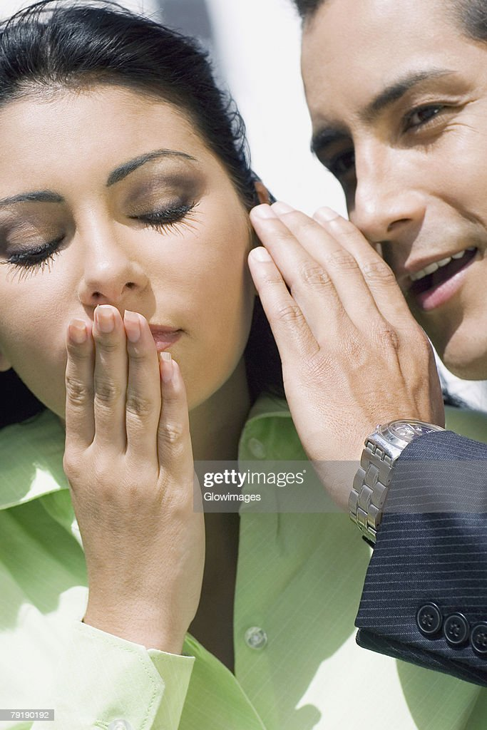 Close-up of a businessman whispering into a businesswoman's ear : Foto de stock