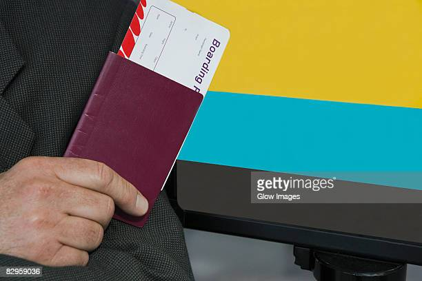 Close-up of a businessman's hand holding a passport with an airplane ticket