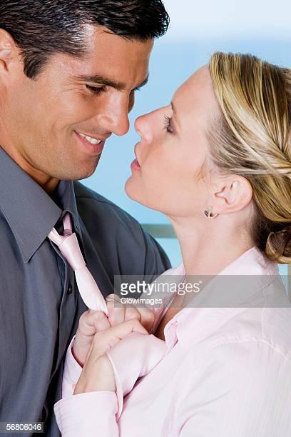 Close-up of a businesswoman adjusting a businessman's tie