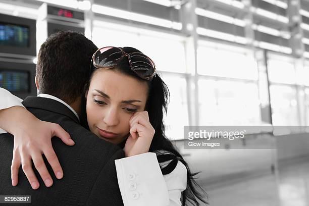 Close-up of a businesswoman embracing a businessman at an airport