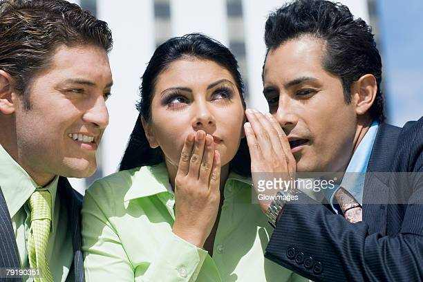 Close-up of a businesswoman gossiping with two businesswomen