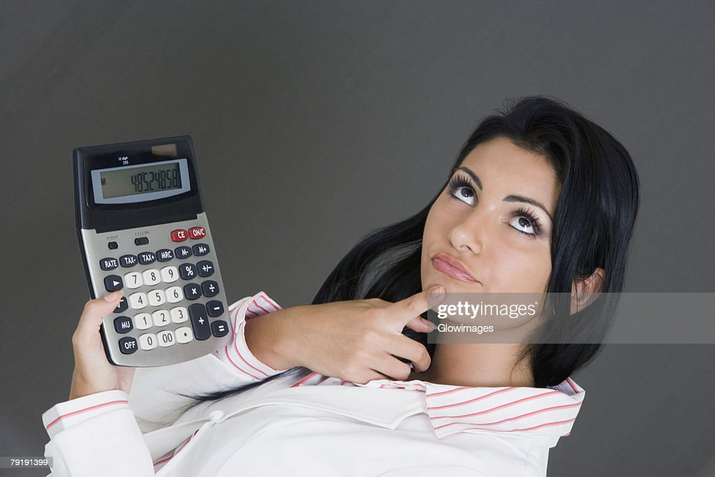 Close-up of a businesswoman holding a calculator and contemplating : Foto de stock