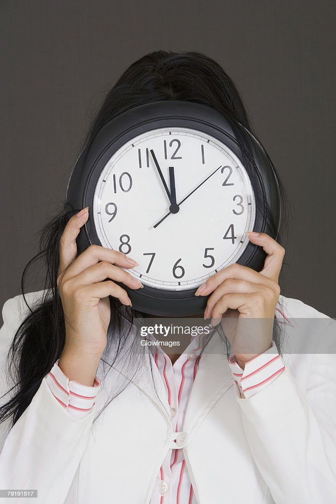 Close-up of a businesswoman holding a clock in front of her face : Stock Photo