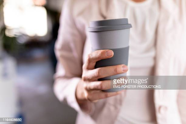 close-up of a businesswoman holding recycable takeaway coffee cup - ems forster productions stock pictures, royalty-free photos & images