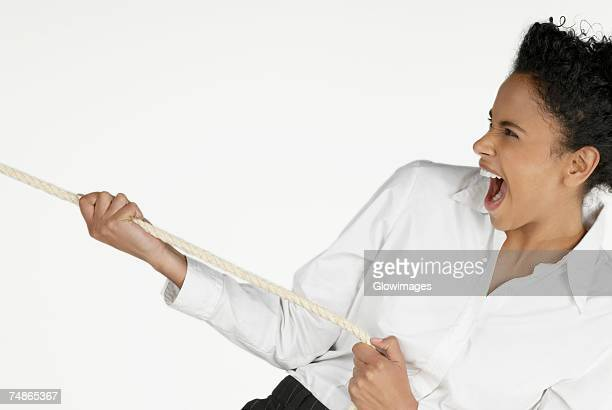 Close-up of a businesswoman pulling a rope and laughing