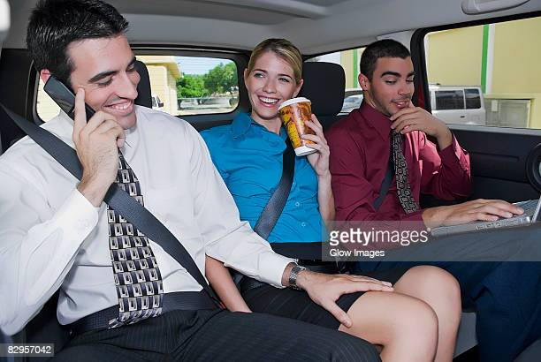 close-up of a businesswoman sitting between two businessmen in a car and smiling - man touching womans leg fotografías e imágenes de stock