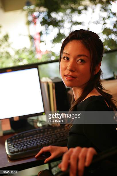 Close-up of a businesswoman sitting in front of a computer