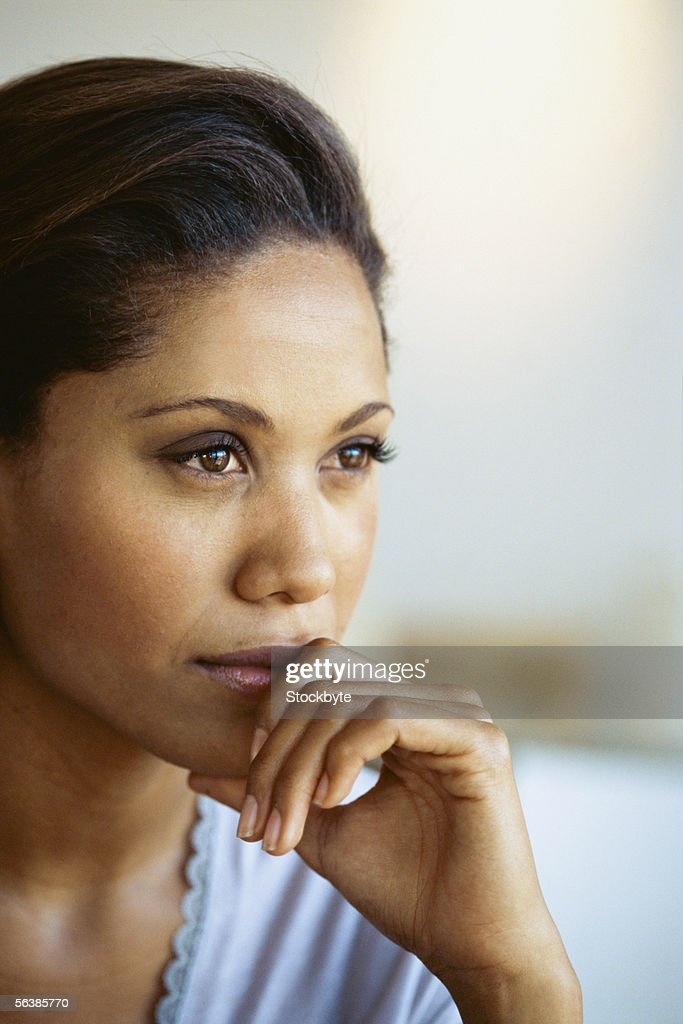 close-up of a businesswoman sitting with her hand on her chin : Stock Photo