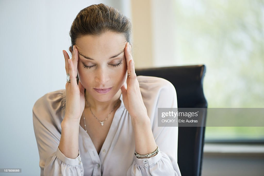 Close-up of a businesswoman suffering from a headache in an office : Stock Photo