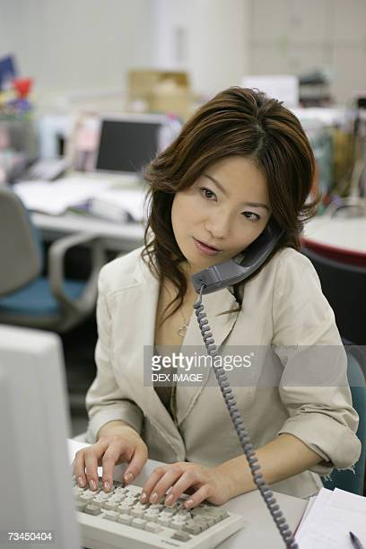 Close-up of a businesswoman talking on the telephone and using a computer
