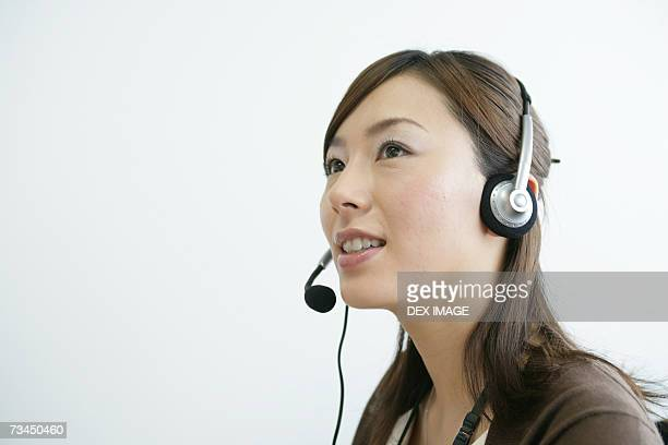 Close-up of a businesswoman using a headset and smiling