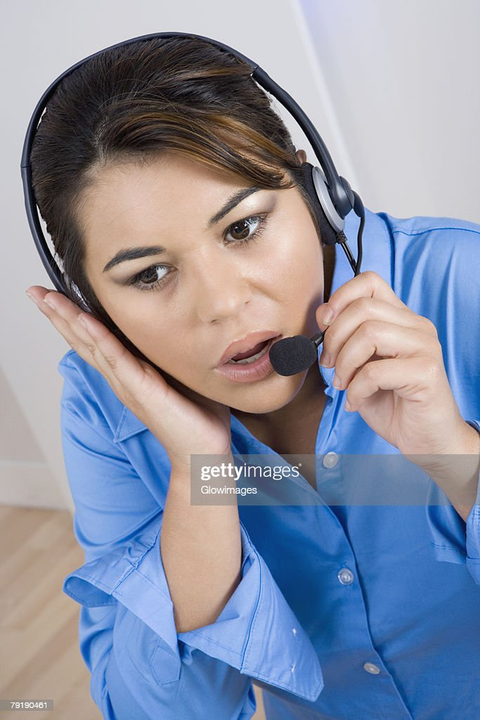 Close-up of a businesswoman wearing a headset and looking away : Foto de stock