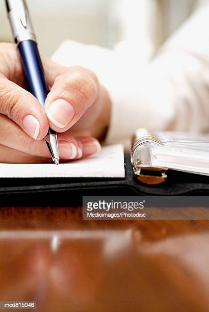 Close-up of a businesswoman's hand writing in a diary