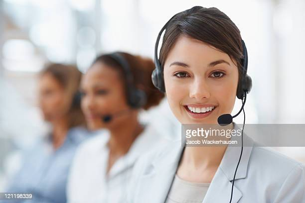closeup of a call center employee with headset at workplace - receptionist stockfoto's en -beelden