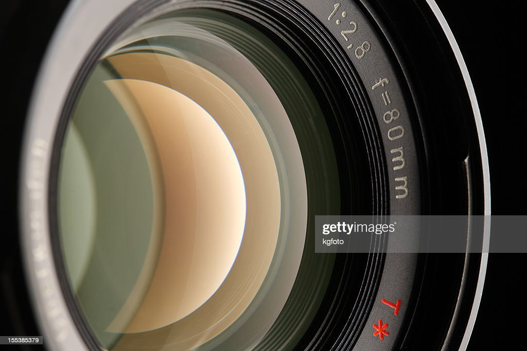 A close-up of a camera lens on a black background : Stock Photo