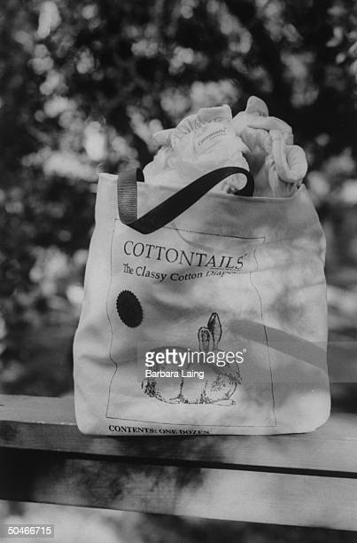 Closeup of a canvas carryall bag emblazoned w rabbit logo for COTTONTAILS the Classy Cotton Diaper overflowing w several diapers from the dozen it...