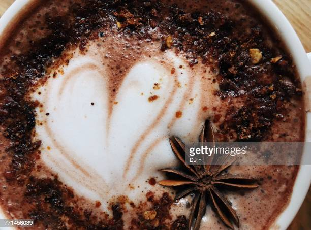 Close-up of a cappuccino coffee with star anise decoration