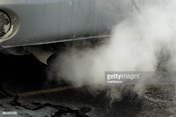 Close-up of a car's tailpipe with smoke coming out