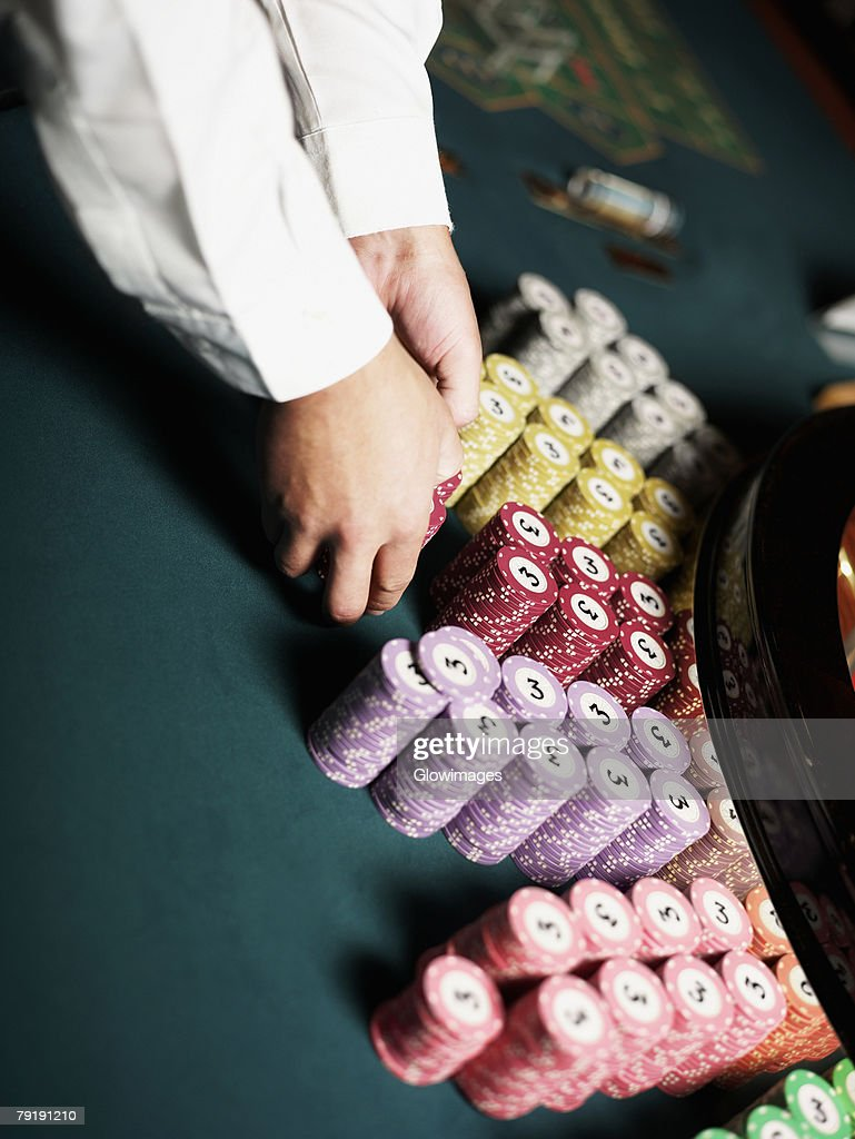 Close-up of a casino worker's hand arranging gambling chips on a gambling table : Stock Photo