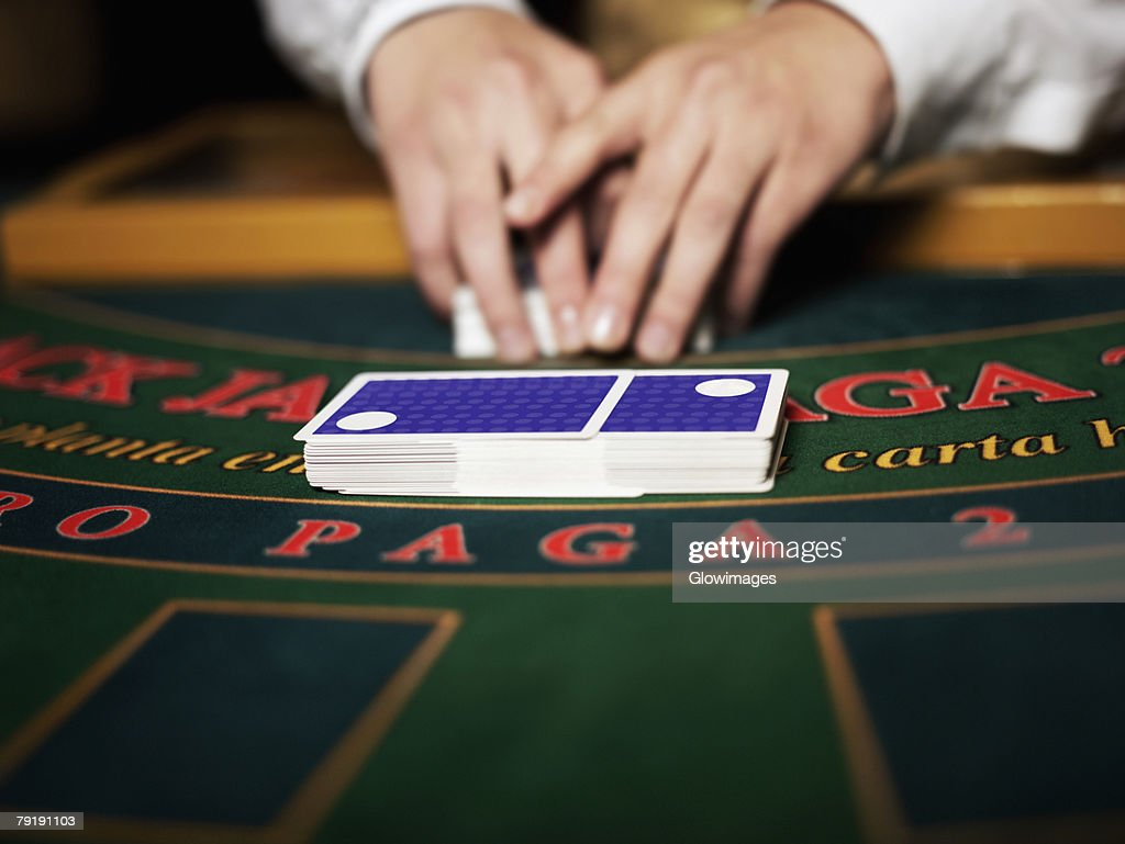 Close-up of a casino worker's hand shuffling playing cards on a gambling table : Foto de stock