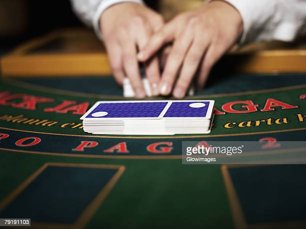 Close-up of a casino worker's hand shuffling playing cards on a gambling table