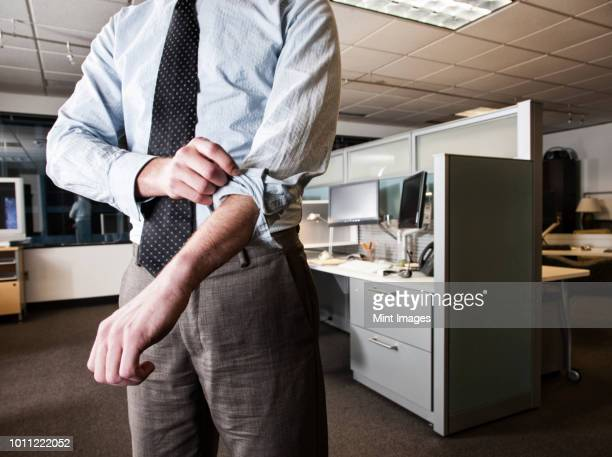 closeup of a caucasian businessman wearing a dress shirt and tie and rolling up his sleeves in his cubicle office. - rolled up sleeves stock pictures, royalty-free photos & images