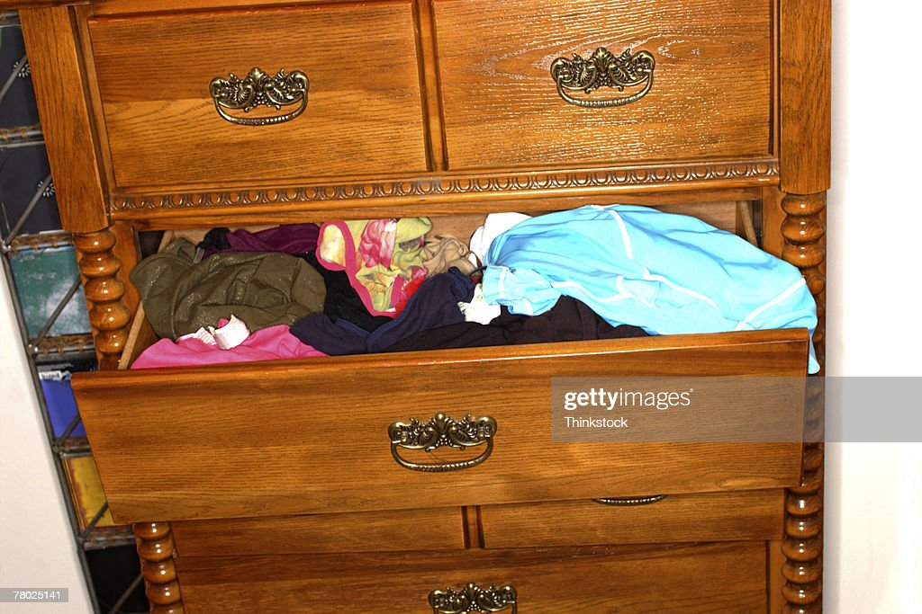 Close-up of a chest of drawers with an open drawer full of clothes. : Stock Photo