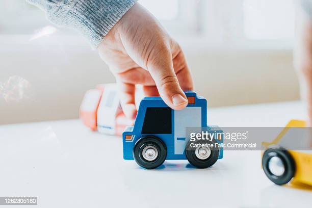 close-up of a child pushing a wooden police van - police station stock pictures, royalty-free photos & images