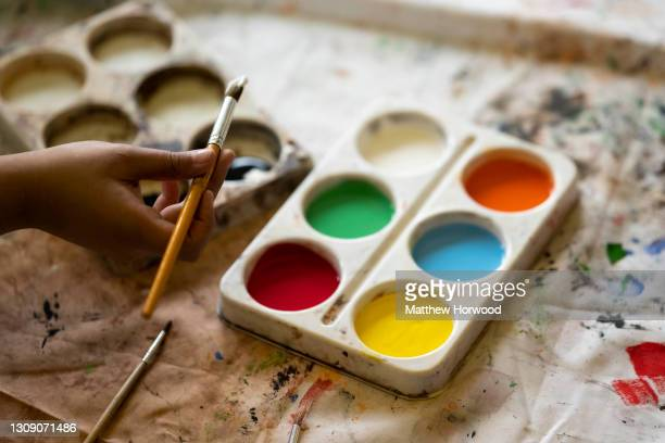 Close-up of a child's hand holding a paint brush at St. Patrick's Catholic Primary School in Grangetown on March 19 in Cardiff, Wales. Children aged...