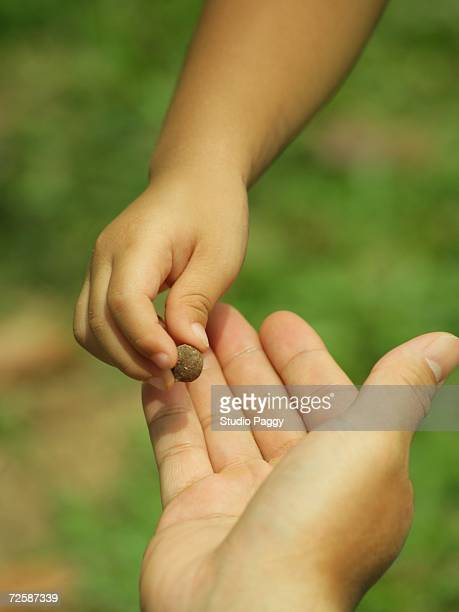 Close-up of a child's hand picking an object from a person's hand