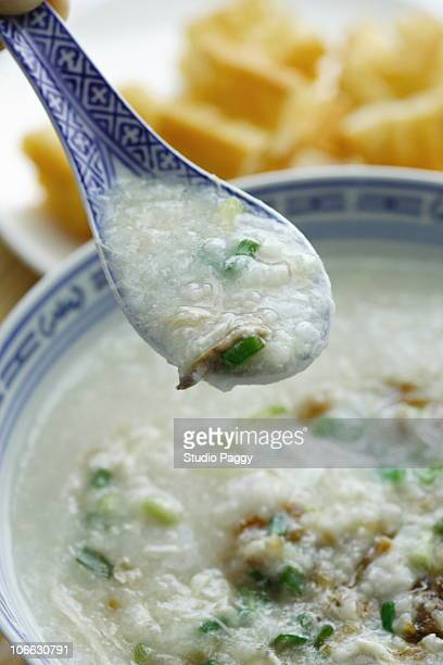 close-up of a chinese chicken rice porridge with a fried ban - congee stock photos and pictures