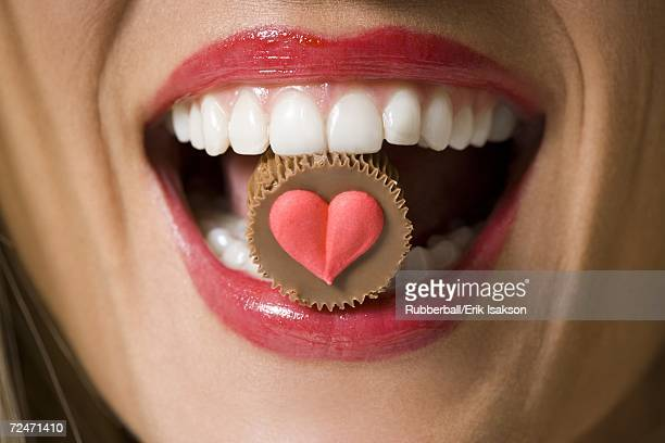Close-up of a chocolate in a young woman's mouth