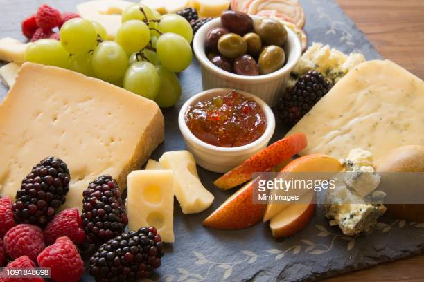 A closeup of a collection of fruits and cheeses.