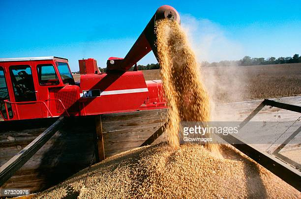 Close-up of a combine loading soy beans into the truck, Midwest, USA