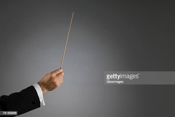 close-up of a conductor's hand holding a conductor's baton - baguette photos et images de collection