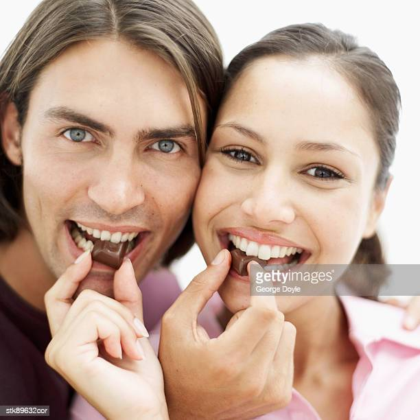 close-up of a couple feeding each other chocolate and smiling - couple chocolate stock pictures, royalty-free photos & images