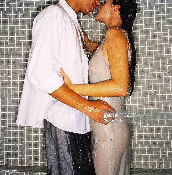 close-up of a couple kissing under a shower - couples kissing shower stock pictures, royalty-free photos & images