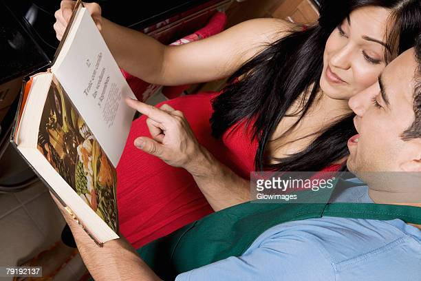 Close-up of a couple reading a cookbook in the kitchen
