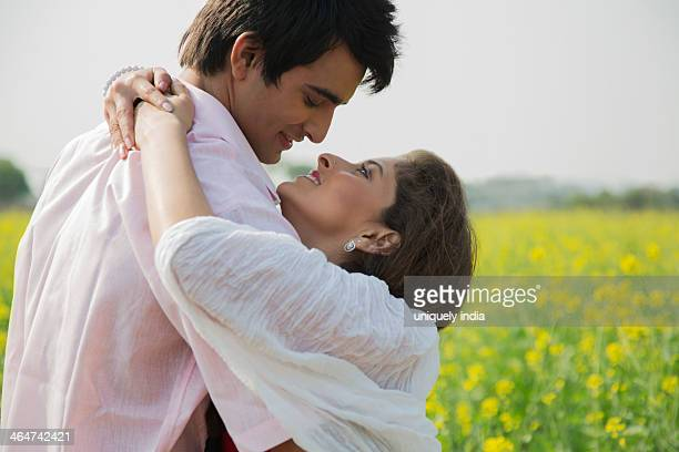 close-up of a couple romancing in a field - indian couples stock pictures, royalty-free photos & images