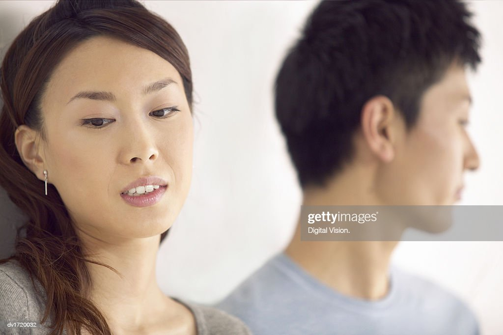 Close-Up of a Couple Sadly Looking Away From Each Other, Focus on Foreground : Stock Photo