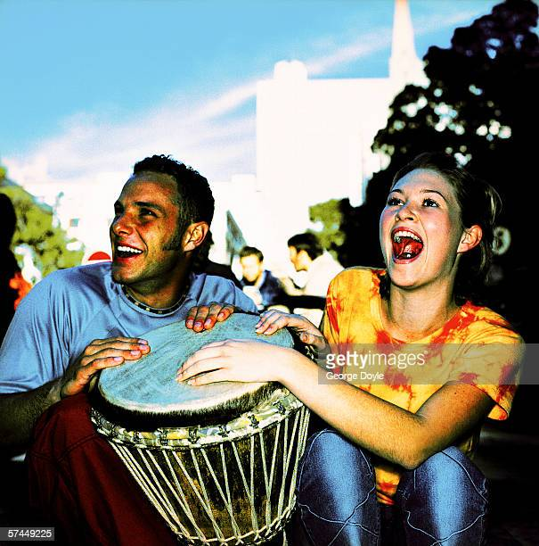 close-up of a couple sitting and beating on a drum