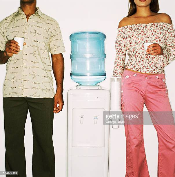 close-up of a couple standing with a water cooler between them